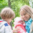 Stock Photo: Young mother with her kids in park.