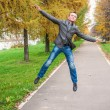 Stock Photo: Young mjumping in autumn park