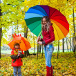 Stock Photo: Happy family with colorful umbrellas in autumn park
