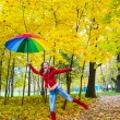 Stock Photo: Pretty girl with colorful umbrellin autumn park