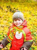 Happy child playing in autumn park — Stock Photo