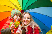 Happy family with colorful umbrella in autumn park — Stock Photo
