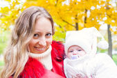 Happy mother and baby in autumn park — Stock Photo