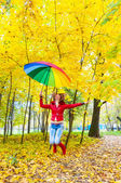 Pretty girl with colorful umbrella jumping in autumn park — Stock Photo