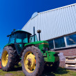 Big green Tractor near warehouse in Holland farm - Stok fotoğraf