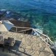Sun-beds and umbrella near clear water, Crete — Stock Video