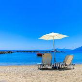 Espreguiçadeiras e guarda-sol na praia — Fotografia Stock