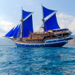 Vintage Wooden Ship with Blue Sails - Stock Photo