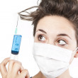 Stock Photo: Young pretty nurse in mask with syringe