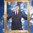 Portrait of businessman holding a golden frame on blue sky with clouds — Stock Photo