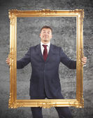 Portrait of businessman holding a golden frame on cement background — Stock Photo