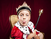 Little boy dressed ad a king on red velvet background — Stock Photo