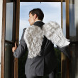 Businessman with angel wings looking through window — Stockfoto