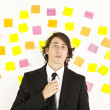 Royalty-Free Stock Photo: Young businessman with postit reminder notes on the background