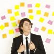 Young businessman with postit reminder notes on the background — Stock Photo