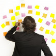 Stock Photo: Young businessman with postit reminder notes on the background