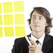Young businessman looking at postit reminder notes — Stock Photo #13761325