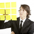 Young businessman looking at postit reminder notes — Stock Photo