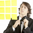 Stock Photo: Young businessman looking at postit reminder notes