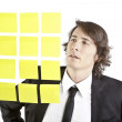 Young businessman looking at postit reminder notes — Stock Photo #13761338