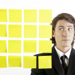 Young businessman looking at postit reminder notes — Stock Photo #13761351