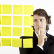 Royalty-Free Stock Photo: Young businessman looking at postit reminder notes