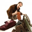 Royalty-Free Stock Photo: Funny vintage young man looking in his suitcase