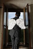 Businessman with angel wings looking through window — Stock Photo