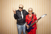 Cool fashion elder couple with electric guitar — Stock Photo