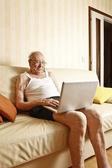 Elder man with laptop — Stock Photo