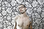 Skinny tattoo guy on floral background — Stock Photo