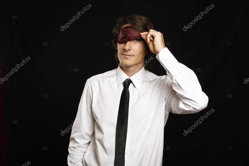 Young businessman looking below sleep mask — Stock Photo #13761508