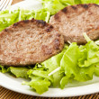 Two hamburger on green lettuce - Stock Photo