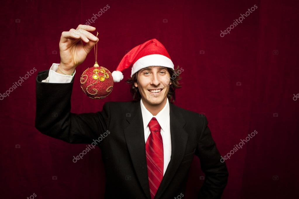 Young funny guy with christmas hat on red valvet background — Stock Photo #13998445
