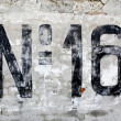 Number sixteen painted on old wall - Stock Photo