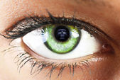 Girl's green eye close up with skull reflected green eye close — Photo