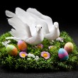 Two doves on colorful field with easter eggs - Foto Stock