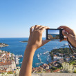 Girl's hand holding digital camera picturing hvar panorama — Stock Photo