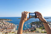Girl's hand holding digital camera picturing hvar panorama — Stock Photo