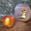 Surrealistic picture of an apple reflecting in the mirror - Stock Photo
