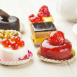 Different sort of beautiful pastry, small colorful sweet cakes - Stockfoto