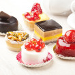 Different sort of beautiful pastry, small colorful sweet cakes — Foto Stock
