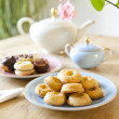 Stock Photo: Plates of pastries and biscuits and tepot on wooden table