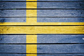 Sweden, swedish flag painted on old wood plank background — Stock Photo