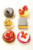 Different sort of beautiful pastry, small colorful sweet cakes — Stock Photo