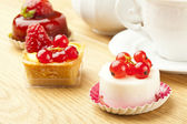 Fruit pastry little cake with tea cup on wooden table — Stock Photo