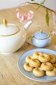 Um prato de biscoitos, um bule de chá e uma flor na mesa de madeira — Fotografia Stock