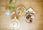 Plates of pastries and biscuits and tea pot on wooden table — Stock Photo