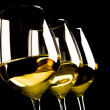 Three glasses of white wine on black background — Stock Photo #14548049