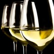 Three glasses of white wine on black background — Stock Photo #14548069